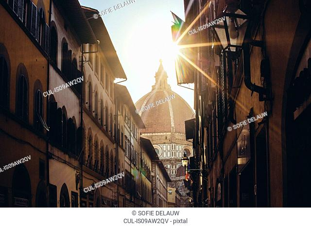 View of sunlit Duomo (Florence Cathedral) from traditional street, Florence, Italy