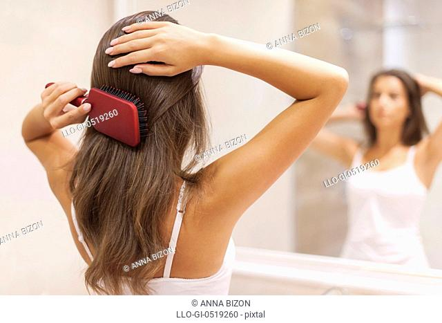 Young woman brushing healthy hair in front of a mirror. Debica, Poland