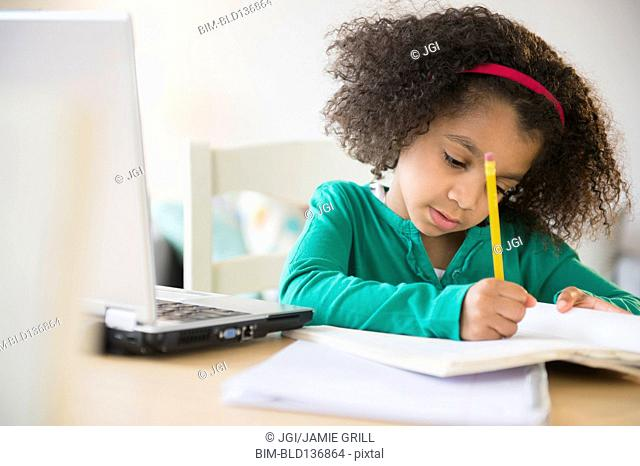 African American girl doing homework with laptop