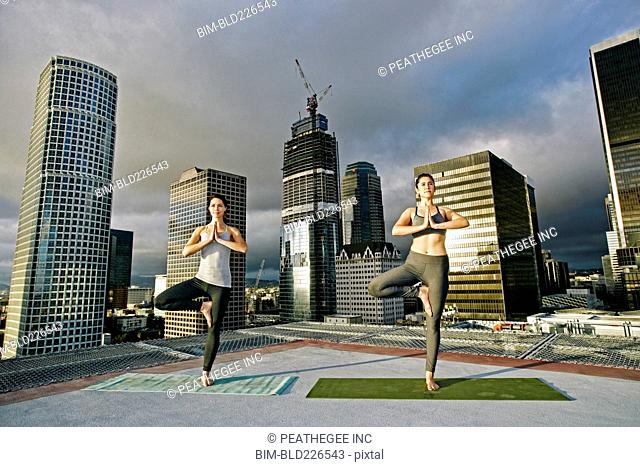 Caucasian women doing yoga urban rooftop