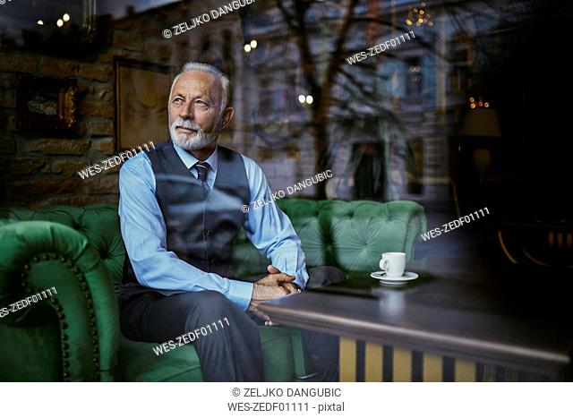 Elegant senior man sitting on couch in a cafe looking out of window