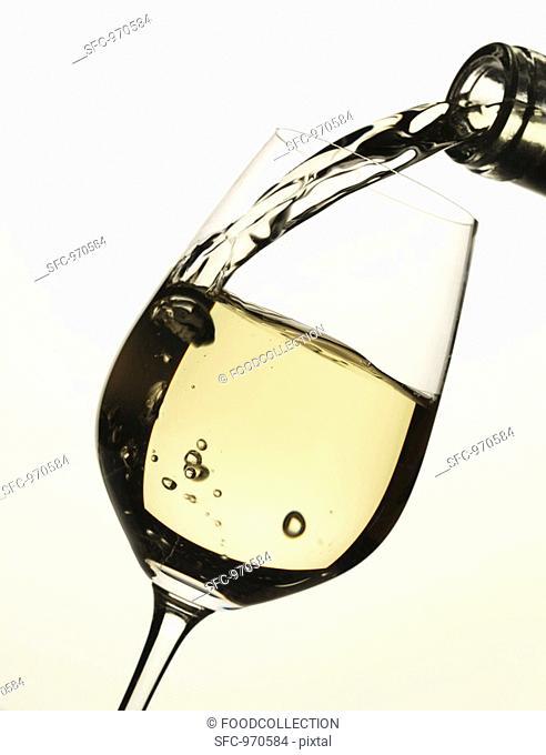 Pouring white wine into glass
