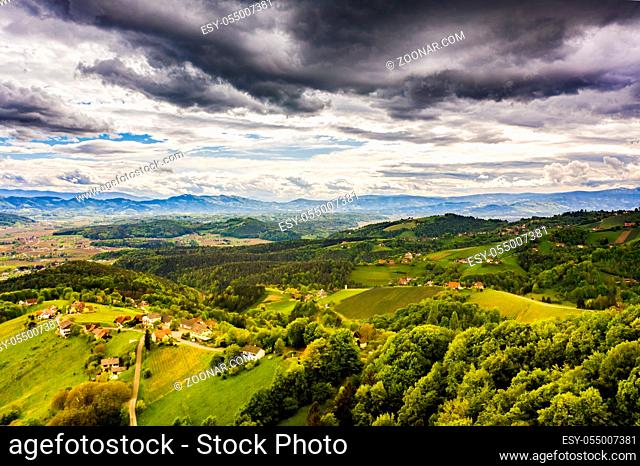 Aerial view of green hills and vineyards with mountains in background. Austria vineyards landscape. Leibnitz area in south Styria, wine country