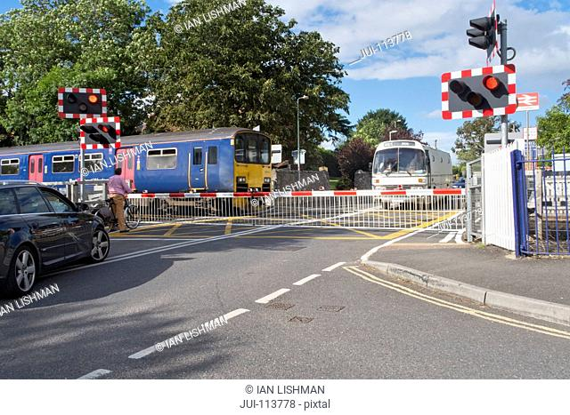 Railway train crossing road with level crossing and bus and car waiting