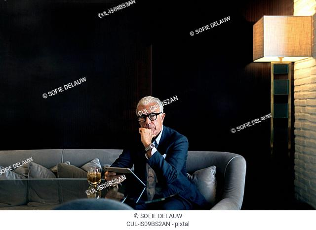 Senior businessman sitting in hotel table using digital tablet, portrait