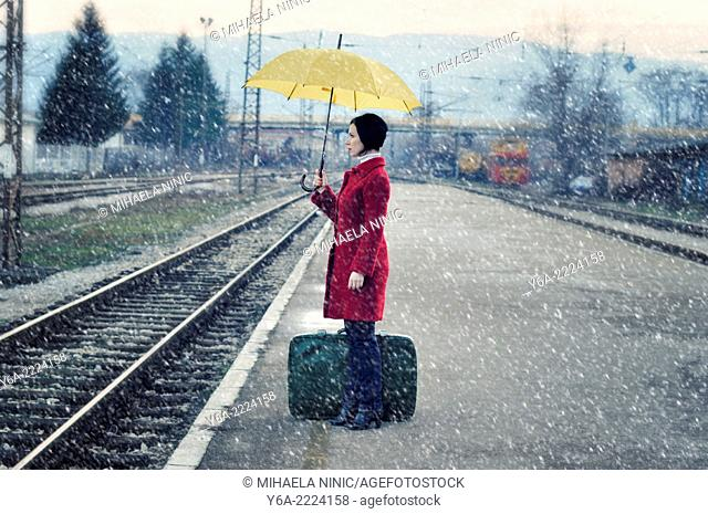 Mid adult woman standing on railroad station platform with suitcase holding umbrella