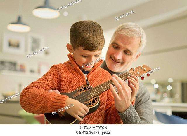 Father teaching son to play the ukulele