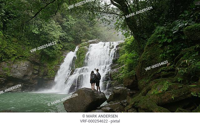 Wide slow motion zoom out of couple admiring waterfall in rain forest / Santa Juana, , Costa Rica