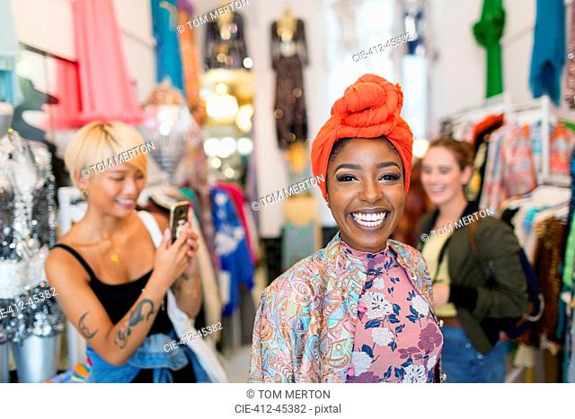 Portrait enthusiastic young woman shopping with friends in clothing store