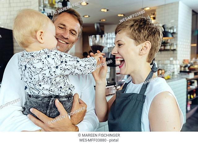 Waitress playing with baby of customer in cafe
