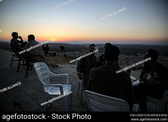14 August 2020, Syria, Arihah: A group of young men gather for drinks and hookah smoking after taking a stroll at Jabal Al-Arbaeen mount during the weekend