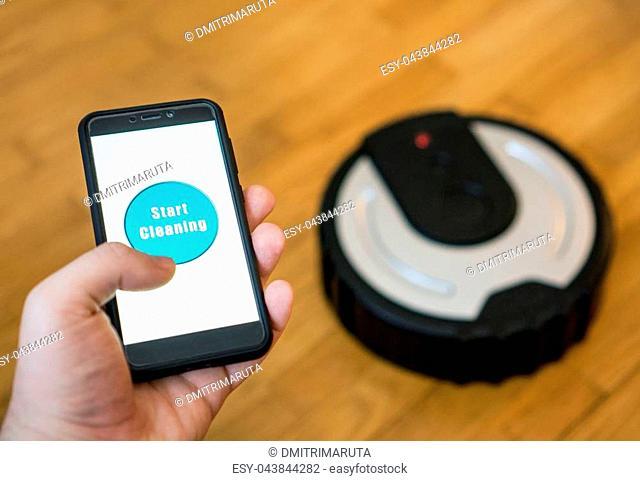 Man using mobile app to control robotic vacuum cleaner