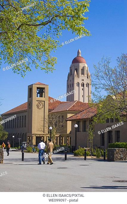 People walking on a street on the Stanford University campus, with Hoover Tower overlooking the clock tower and at the school of education  The sandstone...