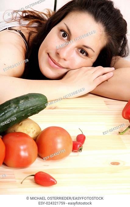 A young hispanic girl in the kitchen between vegetables