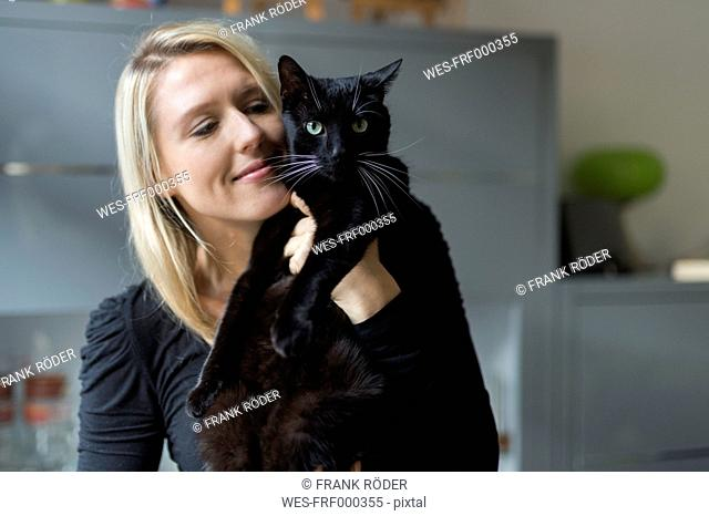 Portrait of smiling blond woman holding her black cat