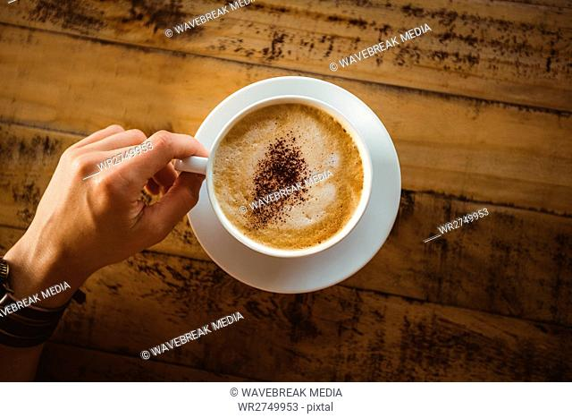 Hands of woman holding cup of coffee