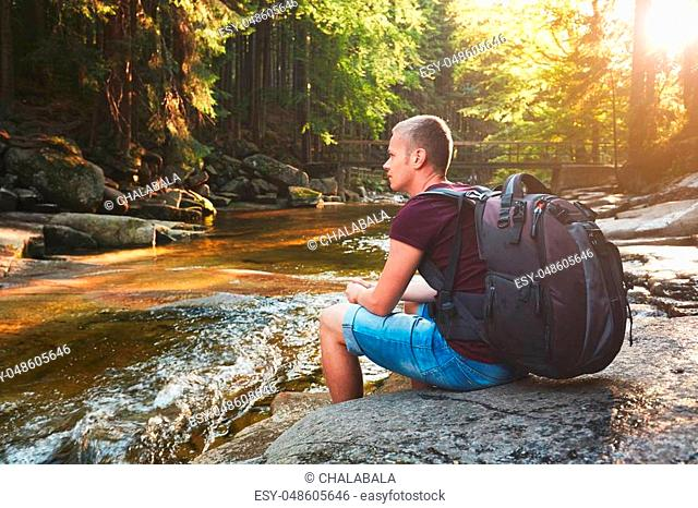 Sunset in pure nature. Traveler with backpack resting on the riverside in forest. National park Krkonose, Czech Republic