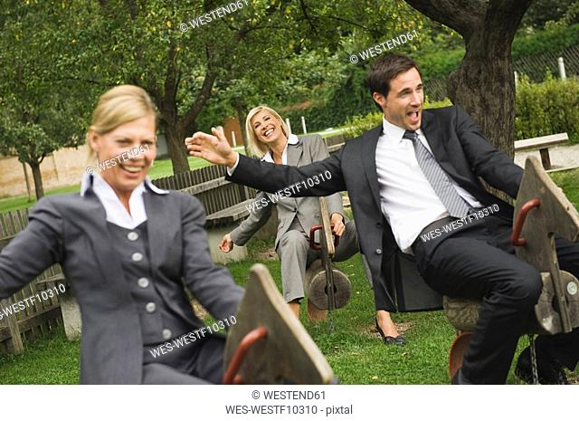Germany, business people riding rocking horses in playground
