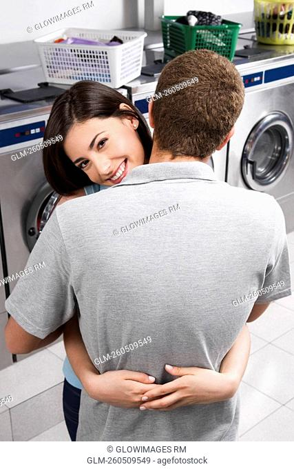 Couple hugging in a laundromat