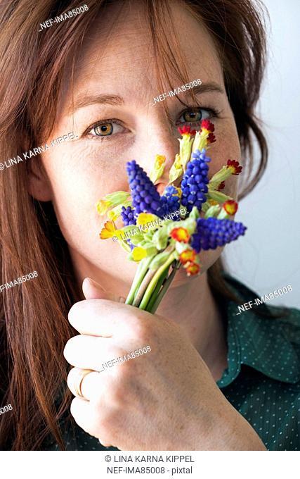 Woman holding bunch of grape hyacinth, close-up, portrait