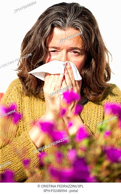Woman with runny nose, having an allergic reaction to pollen from flowers