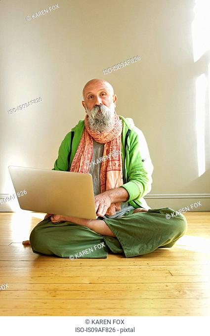Senior man using laptop in lotus position