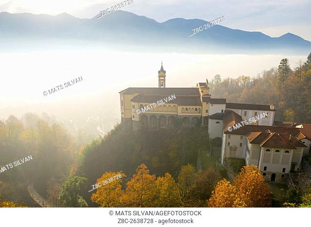 Monastery Madonna del Sasso with sea of fog and sunlight and swiss alps in Locarno, Switzerland