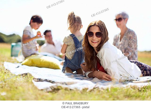 Portrait smiling woman laying on blanket in sunny field with family