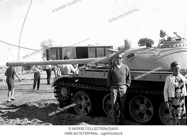 Tourists posing in front of an Israeli tank, while other visitors in the background take photographs of surrounding army vehicles, November, 1967