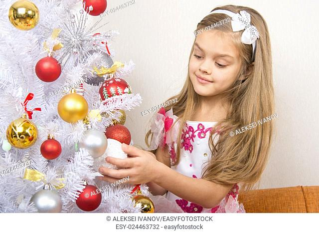 Seven-year girl in a beautiful dress treats Christmas toys