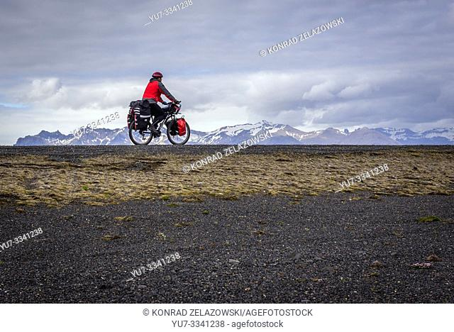 Tourist riding bike on Route 1 national road in south part of Iceland