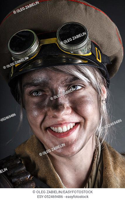 Nuclear post apocalypse life after doomsday concept. Smiling face of grimy female survivor. Studio portrait on black background