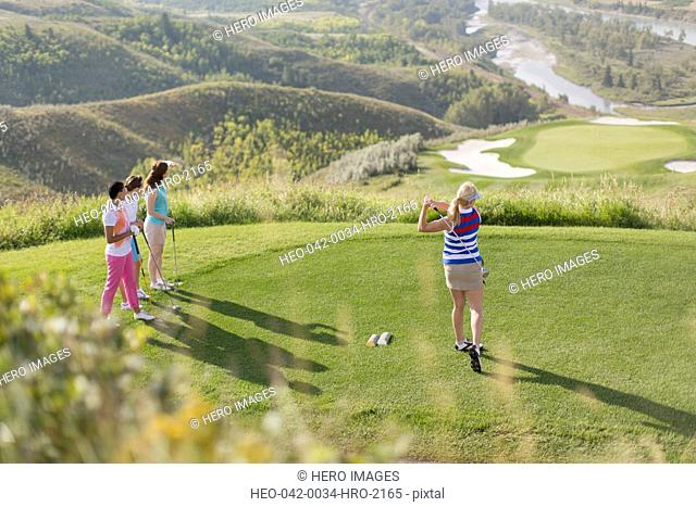 female golfer driving golf ball while golfer friends watch