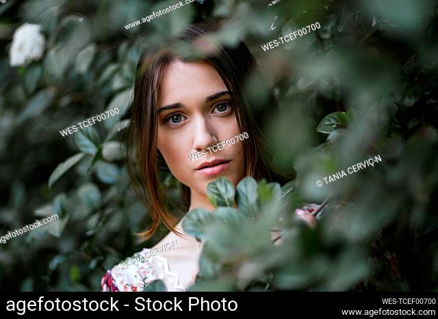 Beautiful woman looking gthrough green leaves
