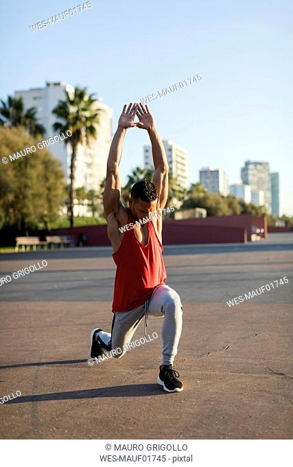 Fit man warming up before workout, doing lunges