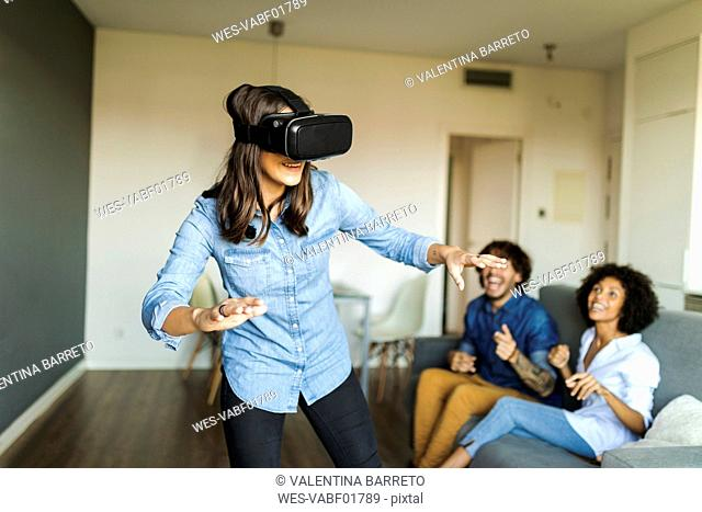 Friends watching woman with VR glasses at home