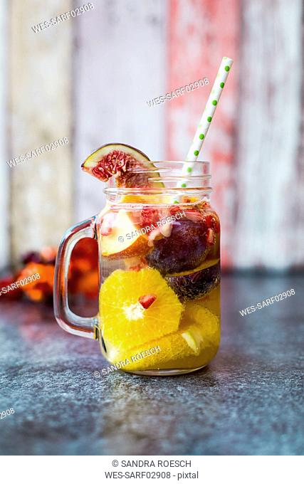 Glass of infused water with orange slices, fig, pomegranate seed, nectarine and plums