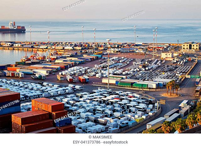 Port terminal with containers, new cars and wagons in the early morning