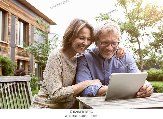 Happy mature couple sharing digital tablet in garden
