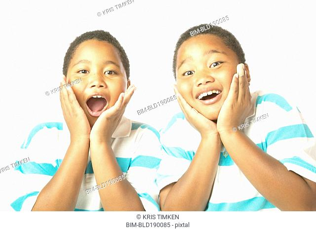Young African twin brothers looking surprised