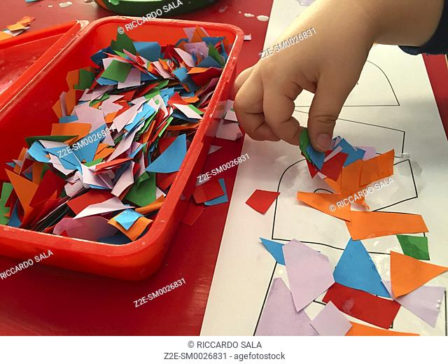 Child's Hands with Brush, Gluing Coloured Shapes onto Pieces of Paper. . .