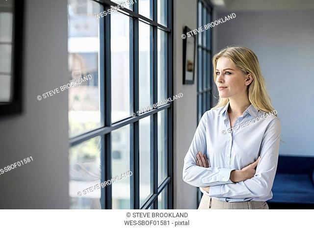 Confident businesswoman standing in office looking out of window