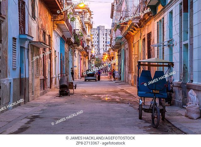 A cycle rickshaw on a street in Centro Habana at dusk. Havana, Cuba