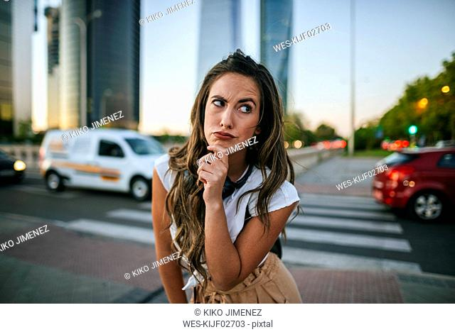 Young woman with doubtful face, skyscrapers in the background