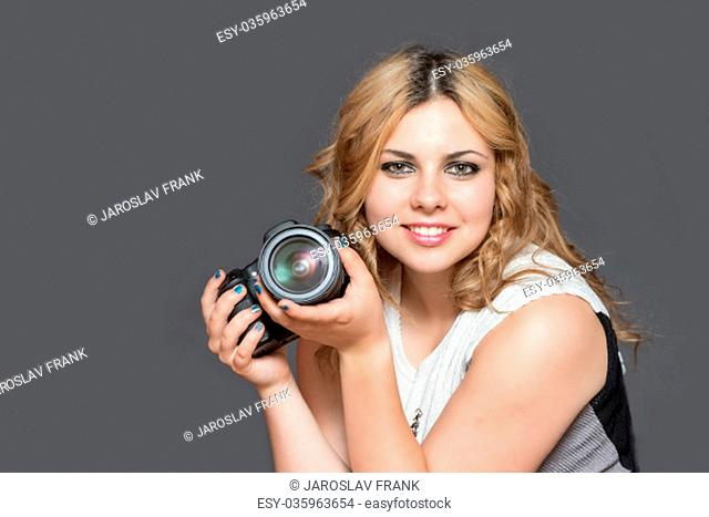 Portrait of smiling brown haired young woman holding a camera in both hands. All potential trademarks are removed. All is on the gray background