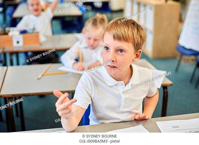Schoolboy counting with fingers in classroom at primary school