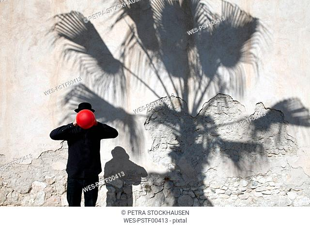Morocco, Essaouira, man wearing a bowler hat holding red balloon in front of his face at a wall