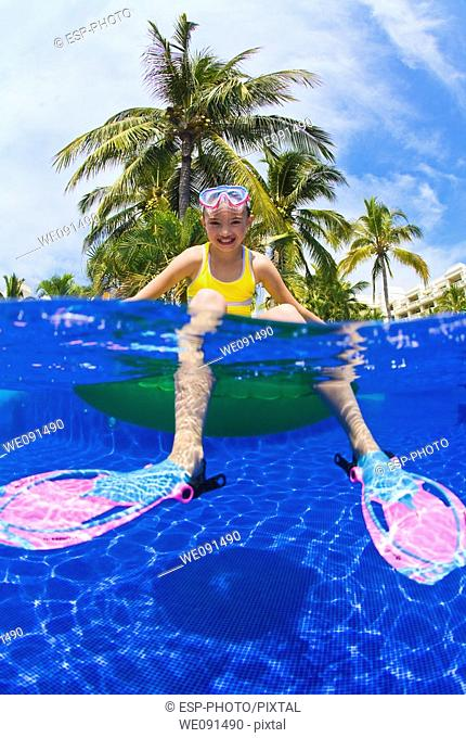 Young girl sitting on float in swimming pool with snorkeling equipment