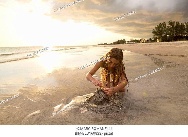 Caucasian girl building sandcastle on beach
