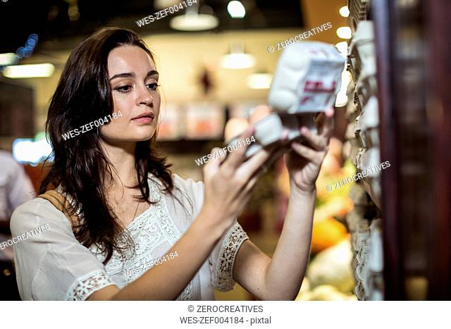 Woman at supermarket shopping for eggs